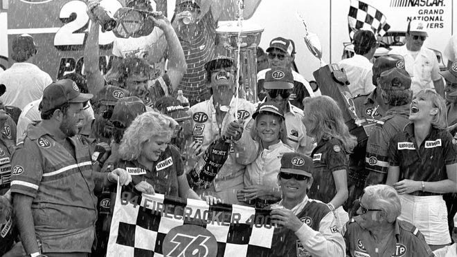 Firecracker 400 winner Richard Petty showers the crowd with champagne in Victory Lane after he won the race July 4, 1984, at Daytona International Speedway. It was the 200th Cup win for Petty. Jann Zlotkin/AP photo