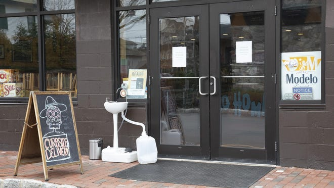 A hand-washing station sits outside Taco Hombre in Warwick on Wednesday. The restaurant is offering curbside delivery to help boost its business after the state ordered restaurants to close all operations except takeout and delivery due to the coronavirus.
