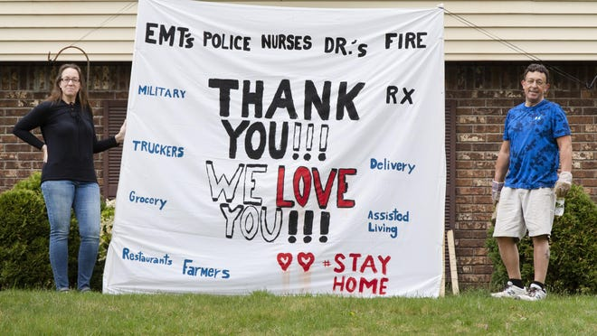 Christin Persico, left, and her boyfriend, Robbie Jacobs, made this support banner displayed in their front yard in Greenwood Lake on Wednesday.