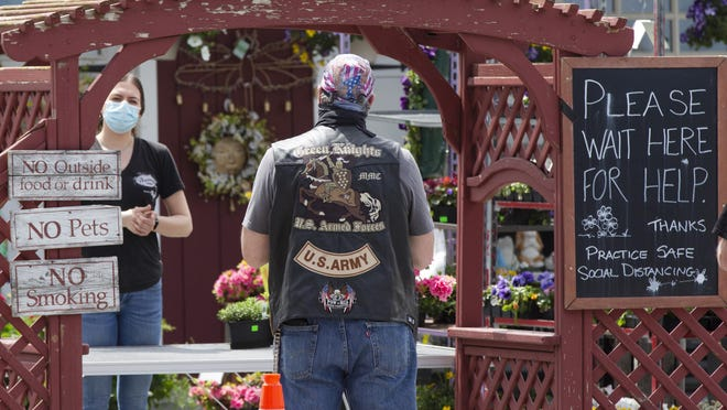 A motorcyclist places a curbside pickup order at Pennings Farm in Warwick on May 2.