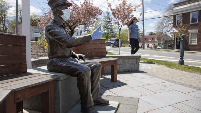The bronze statue of firefighter Richie Reynolds wears PPE at the corner of Union and Clintion Streets in the Village of Montgomery.