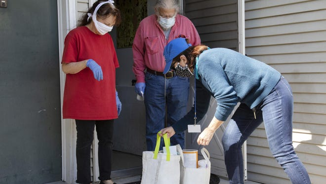Volunteer Jean Ciappa delivers bags of groceries delivered to Richard Ferrar and Yvonne Muller in Warwick.
