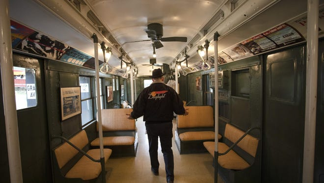 """Tom Zoufaly wears his """"Daylight"""" jacket while walking through a 1937 New York City subway car located behind his home in Warwick. Zoufaly has an enthusiasm for old trains and other antique modes of transportation."""