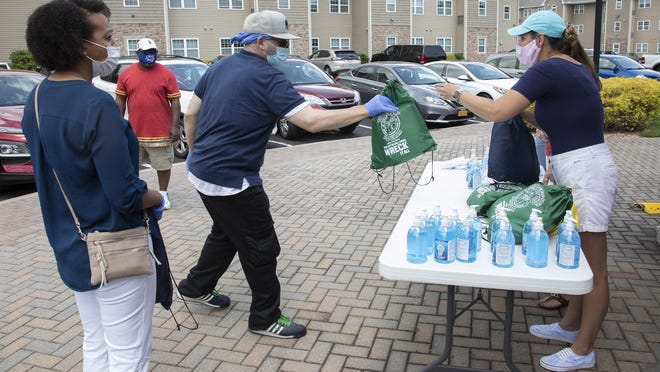 Orange County Community Outreach and Law department workers hand out PPE bags to Middletown residents who stopped by at Liberty Green Apartments in Warwick June 6.