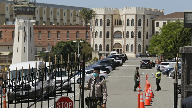 A correctional officer closes the main gate at San Quentin State Prison in San Quentin, Calif., on Thursday.