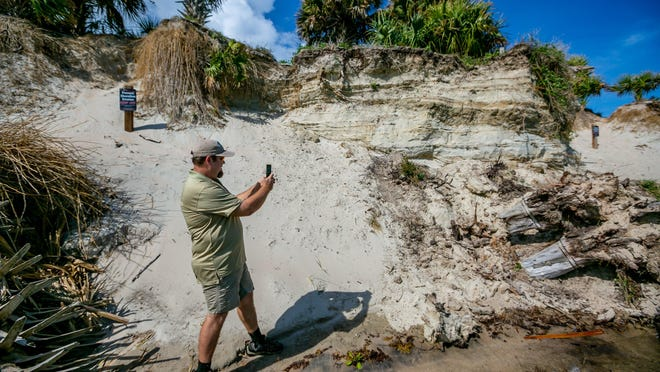 Bureau of Land Management site manager Peter DeWitt documents a new area of erosion next to signs warning visitors to keep off the shoreline surrounding the Jupiter Inlet Lighthouse Outstanding Natural Area Wednesday in Jupiter on February 12, 2020.