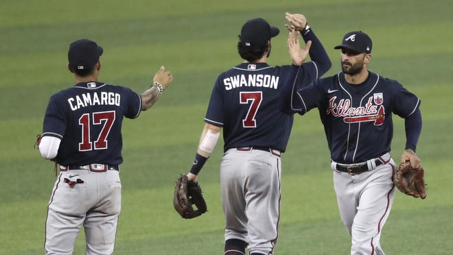 Atlanta Braves' Johan Camargo (17), Dansby Swanson (7), and Nick Markakis, right, celebrate after defeating the Miami Marlins in a baseball game, Sunday in Miami.