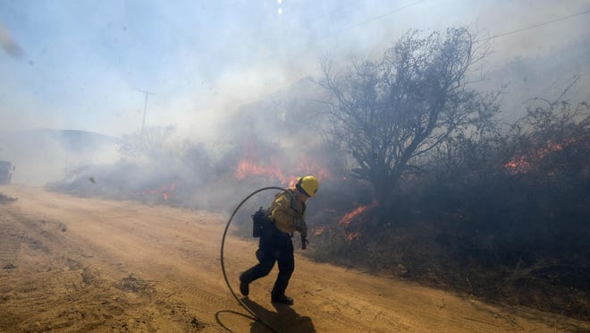 A firefighter runs as wind blows at the Apple Fire in Banning, Calif., Sunday, Aug. 2, 2020.