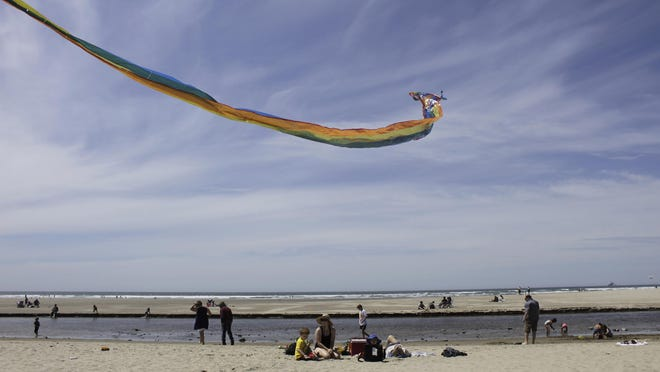 In this Thursday, May 28, 2020, photo Gwen Partlow and her sons, Cameron, 5, and Casey, 2, fly a kite on the beach during the coronavirus outbreak in Cannon Beach, Ore. With summer looming, Cannon Beach and thousands of other small, tourist-dependent towns nationwide are struggling to balance fears of contagion with their economic survival in what could be a make-or-break summer.