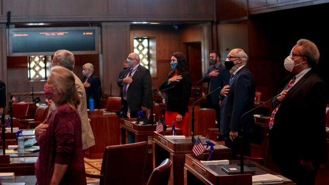 State senators stand and recite the Pledge of Allegiance during a special session called to address police reform and coronavirus concerns at the Oregon State Capitol on Wednesday.