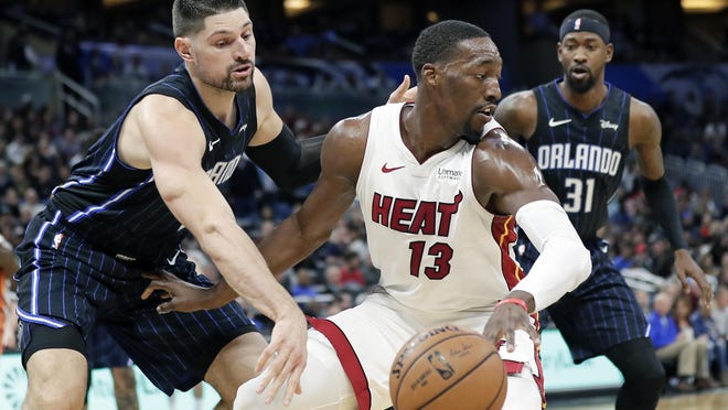 Miami Heat forward Bam Adebayo (13) tries to get around Orlando Magic center Nikola Vucevic, left, and guard Terrence Ross (31) during the first half of a Feb. 1 game in Orlando, Fla.