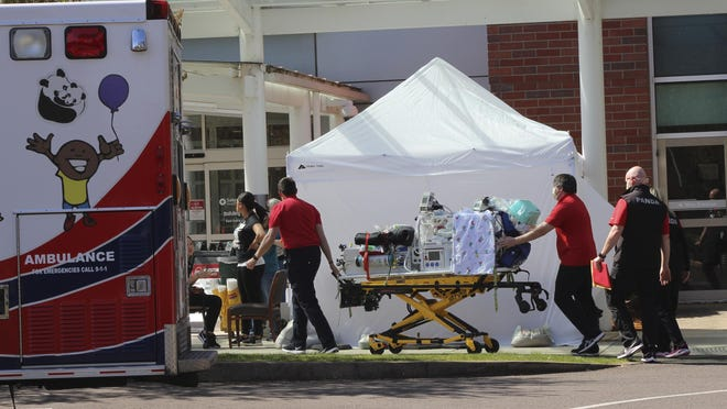 Health care workers in April wheel a gurney into Salem Hospital's emergency room. More people have died this year in the state than normal, but the increase  has outnumbered those attributed to COVID-19.