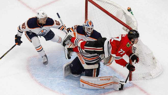 Chicago Blackhawks' Kirby Dach (77) flies past Edmonton Oilers' Caleb Jones (82) and goaltender Mikko Koskinen (19) during the second period on Wednesday.
