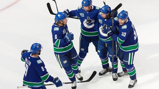 Vancouver Canucks' J.T. Miller (9), Brock Boeser (6), Elias Pettersson (40), Quinn Hughes (43) and Bo Horvat (53) celebrate a goal against the Minnesota Wild  during the third period on Tuesday.