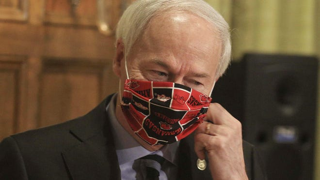 In this April 27 file photo, Gov. Asa Hutchinson takes off his Arkansas Razorbacks facemark as he arrives for the daily coronavirus briefing at the state Capitol in Little Rock. Hutchinson issued the order Thursday, July 16 effective Monday, July 20, requiring people to wear masks in public throughout the state, which is dealing with a surge in coronavirus cases. The governor issued the order after weeks of resisting such a requirement.