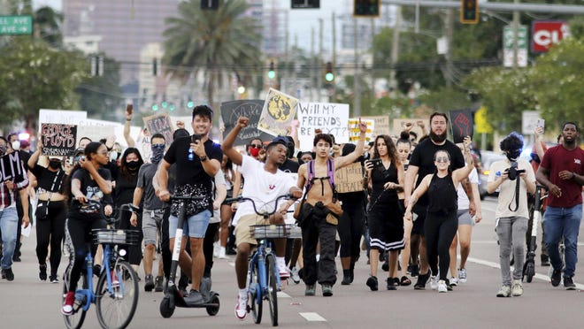 Protesters move down W. Kennedy Blvd. to join a larger gathering of protesters on Tuesday in front of the Fox 13 Tampa Bay news station in Tampa.
