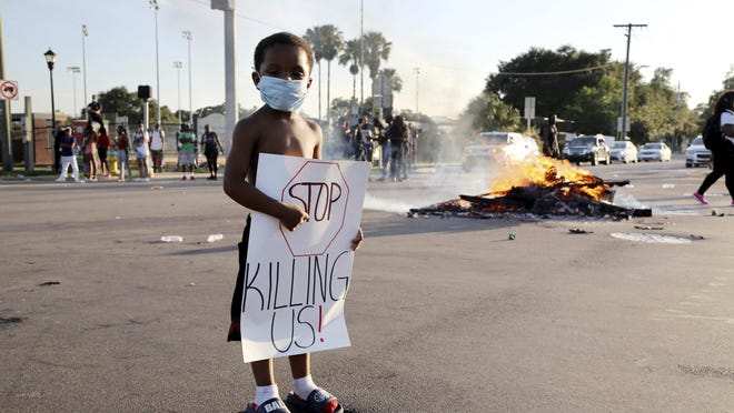 Mychael Latimer Jr., 3, stands at an intersection where the road remained closed during a protest on Sunday in Tampa over the death of George Floyd. Many parents of all races are struggling with having conversations with their children after a week of outrage and sadness that spilled into streets worldwide after video of Floyd's death emerged.