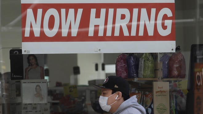 "A man wearing a mask walks under a ""Now Hiring"" sign at a CVS Pharmacy in San Francisco."