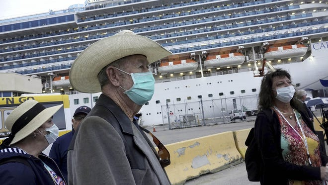 Jana Harrelson, left, Ronny Young, and Karla Weston, right, all of Port St. Joe, Florida, disembark from the Caribbean Princess at Port Everglades on March 11. The cruise ship was been given federal permission to dock in Florida after testing of two crew members cleared them of coronavirus.