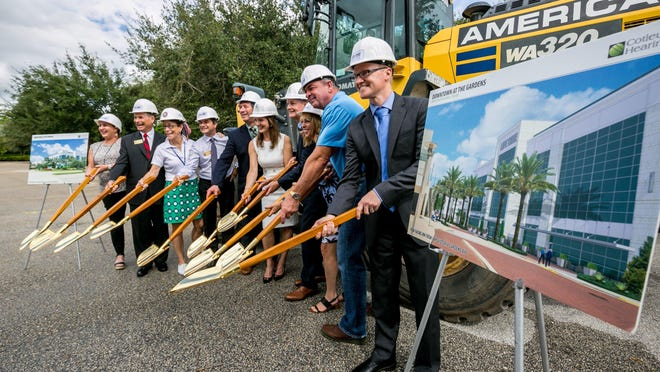 Aaron Koehler, right, vice president of development for Life Time Athletic, breaks ground with local officials Tuesday on a new resort-style health club at Downtown at the Gardens. The 117,000-square-foot facility will feature exercise classes, spa services and a rooftop bistro, among other amenities.