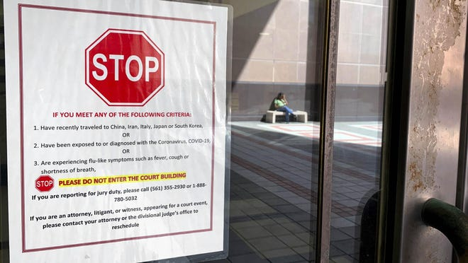 Signs posted on the doors of the Palm Beach County Courthouse Friday afternoon, March 1, 2020 tell people to stay out if they have recently traveled to China, Iran, Italy, Japan or South Korea; or if they have been exposed to or diagnosed with coronavirus; or if they are experiencing flu-like symptoms.