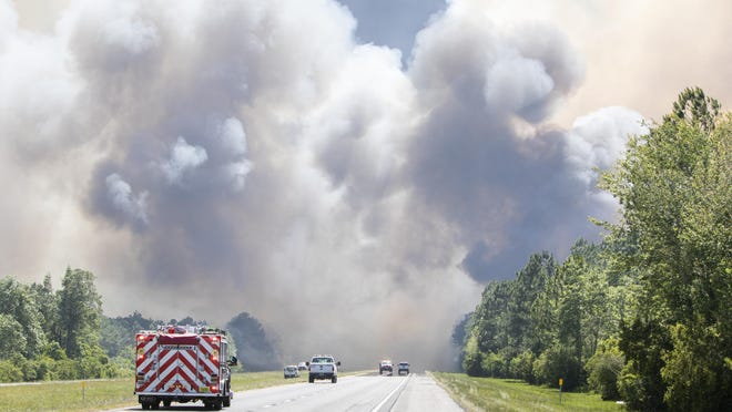 In this Wednesday, May 6 photo, emergency vehicles are stopped due to a large wildfire in Milton, Fla. Firefighters in the Florida Panhandle were battling wildfires that have forced some 1,600 people to evacuate from their homes. Smoke from the fires caused officials to close a stretch of Interstate 10 in both directions Thursday.