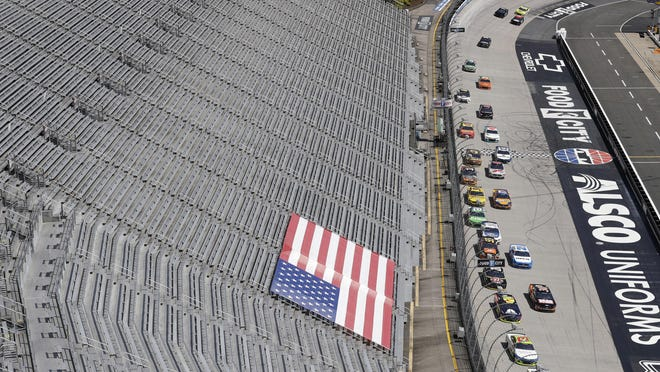 In this May 31 photo, cars speed past empty stands during a NASCAR Cup Series race at Bristol Motor Speedway in Bristol, Tenn. This weekend, at Homstead-Miami Speedway, 1,000 spectators will be in attendance. The race will be the first professional US sports event with a live audience since mid-March.