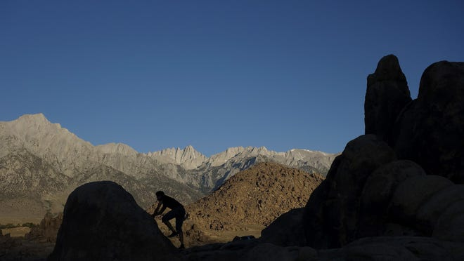 This June 23, 2018, file photo shows Cyril Jay-Rayon scrambling up a rock in the Alabama Hills in Lone Pine, Calif. The rethinking of place names in light of U.S. racial history has turned to California's Alabama Hills, a distinctive high-desert formation named for a Confederate warship.
