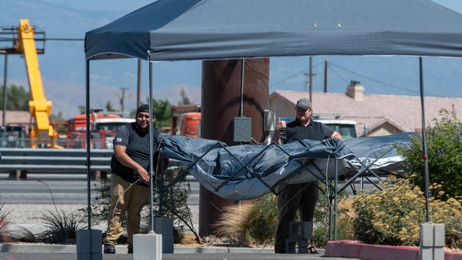 Employees set up a canopy in front of Cracker Barrel in Victorville on Saturday, July 4, 2020.
