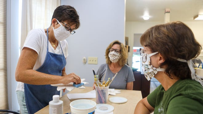 Studio Clay owner Stacey Woolf demonstrates a technique for applying glaze to ceramics for Debbie Frank of Ravenna, center, and Lori Babbey of Paris Township.