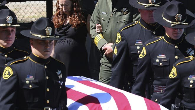 Faviola Del Real holds onto the arm of Santa Cruz County Sheriff Jim Hart as she follows the flag-draped coffin of her husband, sheriff's Sgt. Damon Gutzwiller, into a memorial service at Cabrillo College on Wednesday in Santa Cruz. Heartbroken mourners on Wednesday praised the deputy who was killed in an ambush, calling him kind, unflappable and funny, the kind of officer that people want to keep a community safe.