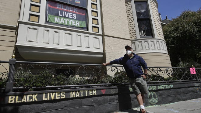 """James Juanillo poses with chalk written outside of his home in San Francisco on Sunday. The CEO of a cosmetic company issued an apology Sunday after she and her husband confronted Juanillo and threatened to call police because he stenciled """"Black Lives Matter"""" in chalk on his San Francisco property, as the couple asserted that they know Juanillo doesn't live there and was therefore breaking the law."""