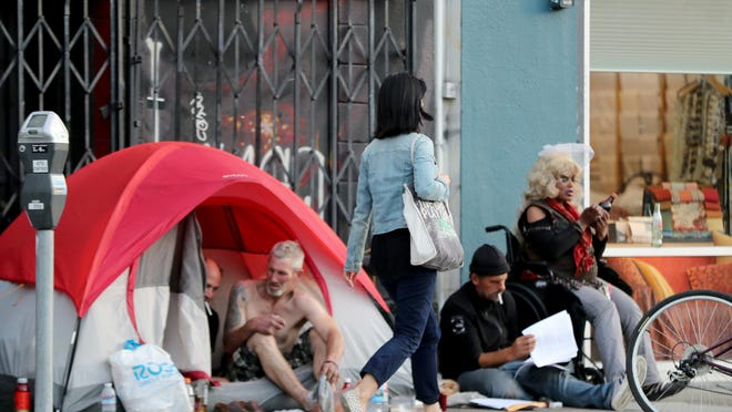 A pedestrian walks a small homeless encampment on Howard Street in San Francisco, Calif., on Thursday, Nov. 1, 2018.