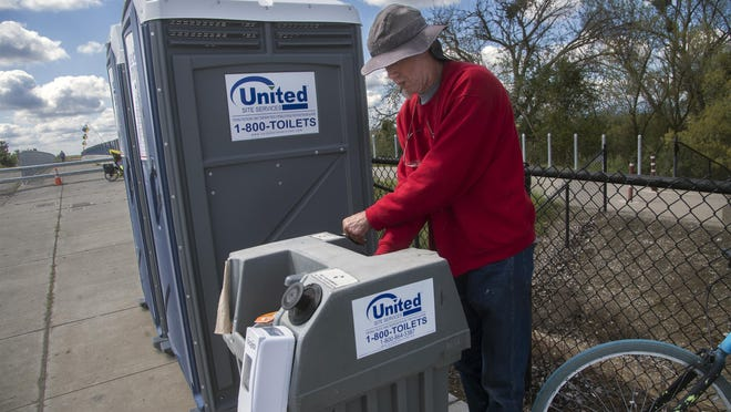 A man who gave his name only as Chris washes his hands at sanitation station set up at the end of Trinity Parkway near White Slough in Stockton. About $4 million of the city's $27 million in COVID-19 relief funds will be used for community well-being expenditures such as personal protective equipment for the community and additional outdoor hygiene stations.