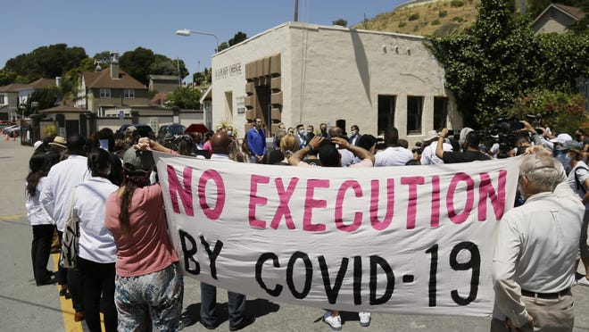 People hold up a banner while listening to a news conference outside San Quentin State Prison on Thursday in San Quentin, where a group of legislators, advocates, academics and public health officials gathered to discuss a COVID-19 outbreak at the facility that has sickened more than 1,400 inmates with six deaths.