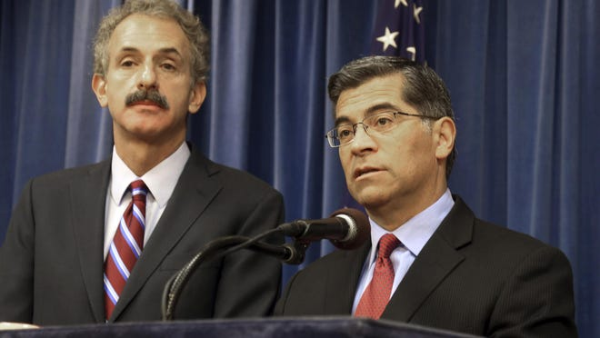 California Attorney General Xavier Becerra, right, and Los Angeles City Attorney Mike Feuer appear at a news conference in Los Angeles in 2018. California on Tuesday became the latest state to sue President Donald Trump over his executive order excluding people in the U.S. illegally from being counted when congressional districts are redrawn after this year's census.