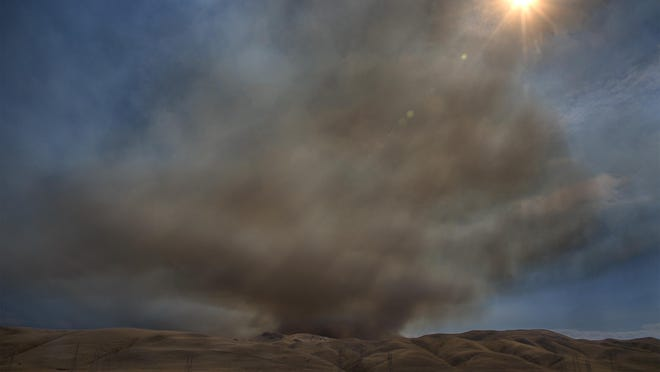 Smoke rises from a wildland fire in Del Puerto Canyon in the hills northwest of Patterson. A column of smoke from the fire drifted as far north as Stockton. According to Cal Fire it's at about 1,851 acres with 0% containment as of Monday morning.