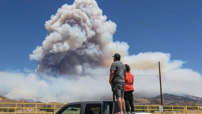 Brutencio and Marina Vidal watch as the Apple Fire burns in the foothills north of Cabazon, August 5, 2020. The Vidals are from Banning, Ca.