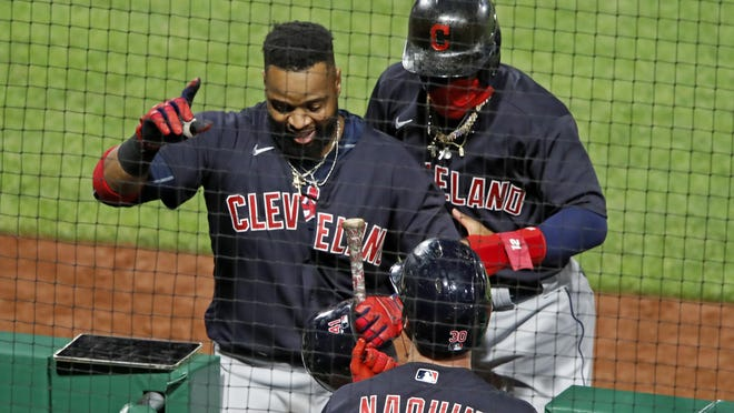 The Indians' Carlos Santana, left, returns to the dugout after hitting a three-run home run off Pittsburgh Pirates relief pitcher Sam Howard during the tenth inning Tuesday.