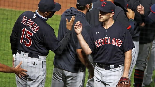 Cleveland Indians starting pitcher Aaron Civale, right, celebrates his complete-game win with coach Sandy Alomar Jr. (15) following a baseball game against the Pittsburgh Pirates in Pittsburgh, Wednesday, Aug. 19, 2020.