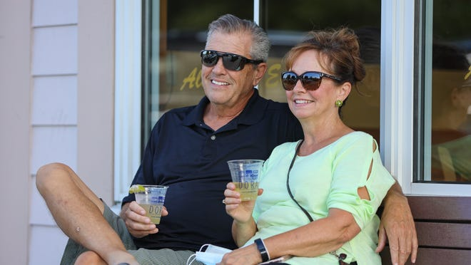 Hudson residents Dave and Karen Maag sit outside Aladdin's Eatery in the city's downtown enjoying their drinks in the new Designated Outdoor Refreshment Area (DORA). People ages 21 and older can purchase alcoholic drinks in special cups and consume the beverages outdoors.