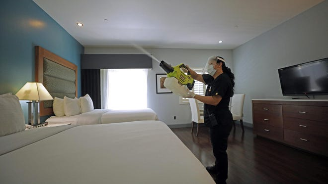 A worker at a hotel in Los Angeles' Studio City section uses a handheld machine to spray a disinfectant fog made of ethanol and hydrogen peroxide.
