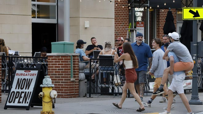 "FILE - In this June 28, 2020, file photo, people gather at tables outside Bar Louie on the Northside of Pittsburgh. Authorities are closing honky tonks, bars and other drinking establishments in some parts of the U.S. to stem the surge of COVID-19 infections â€"" a move backed by sound science about risk factors that go beyond wearing or not wearing masks."