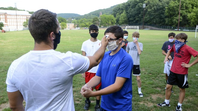 Head coach Zachary Reichert, left, takes Nicholas Giuffre's temperature prior to the start of Pottsville's boys' soccer practice at Alumni Field in Pottsville, Pa., Thursday, Aug. 6, 2020. During a press conference Thursday, Gov. Tom Wolf recommended that no sports take place until January 1, 2021.