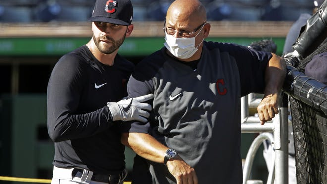 The Indians' Tyler Naquin, left, squeezes past manager Terry Francona during batting practice before an exhibition game last week.