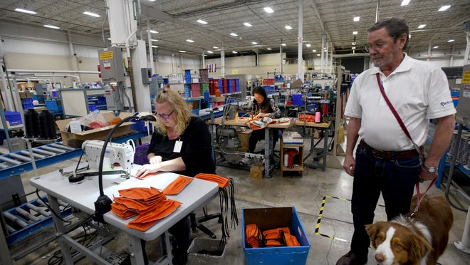 Coastal Pet Products, which shifted some of its resources to remain operating as an essential business during the COVID-19 crisis, received assistance from the federal Paycheck Protection Program. Coast Pet associate Carole Boone, left, is seen sewing masks as company co-founder Jim Stout, with dog Stryker, look on.