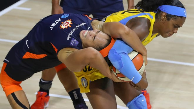 Connecticut Sun's Brionna Jones, left, reaches back to tie up a rebound with Chicago Sky's Cheyenne Parker during the second half of a WNBA basketball game Saturday, Aug. 8, 2020, in Bradenton, Fla.