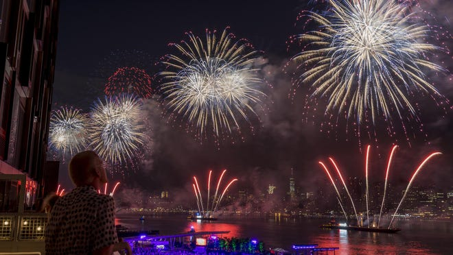 New York City residents watch a Fourth of July fireworks show in 2017. This year's shows from the Big Apple, in a format altered by the pandemic, will be available for viewing at 8 tonight on NBC.