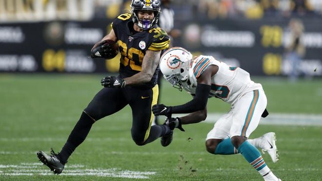 Pittsburgh Steelers running back James Conner (30) looks to get past Miami Dolphins defensive back Chris Lammons during Conner's 145-yard rushing game on Oct. 28, 2019.