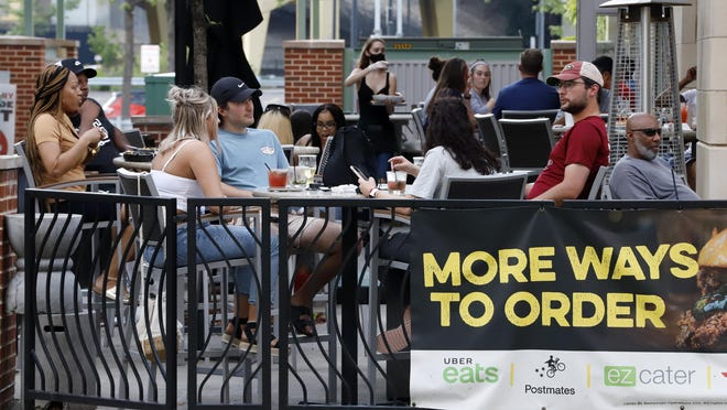 People sit at tables outside Bar Louie on Pittsburgh's North Side on June 28. In response to the recent spike in COVID-19 cases in Allegheny County, linked to young people traveling out of state and visiting bars and restaurants, health officials are ordering all bars and restaurants in the county to close for one week and banning gatherings of 25 people or more.